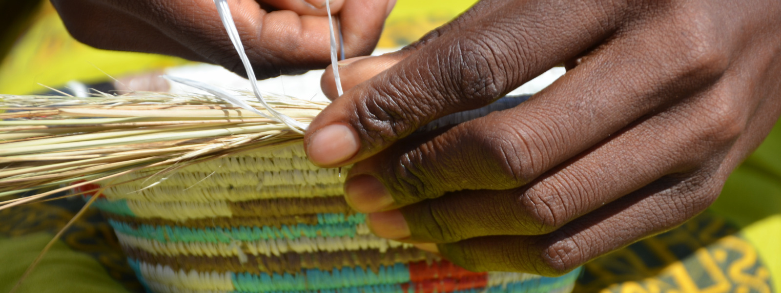 Woman's hand weaving brightly colored basket