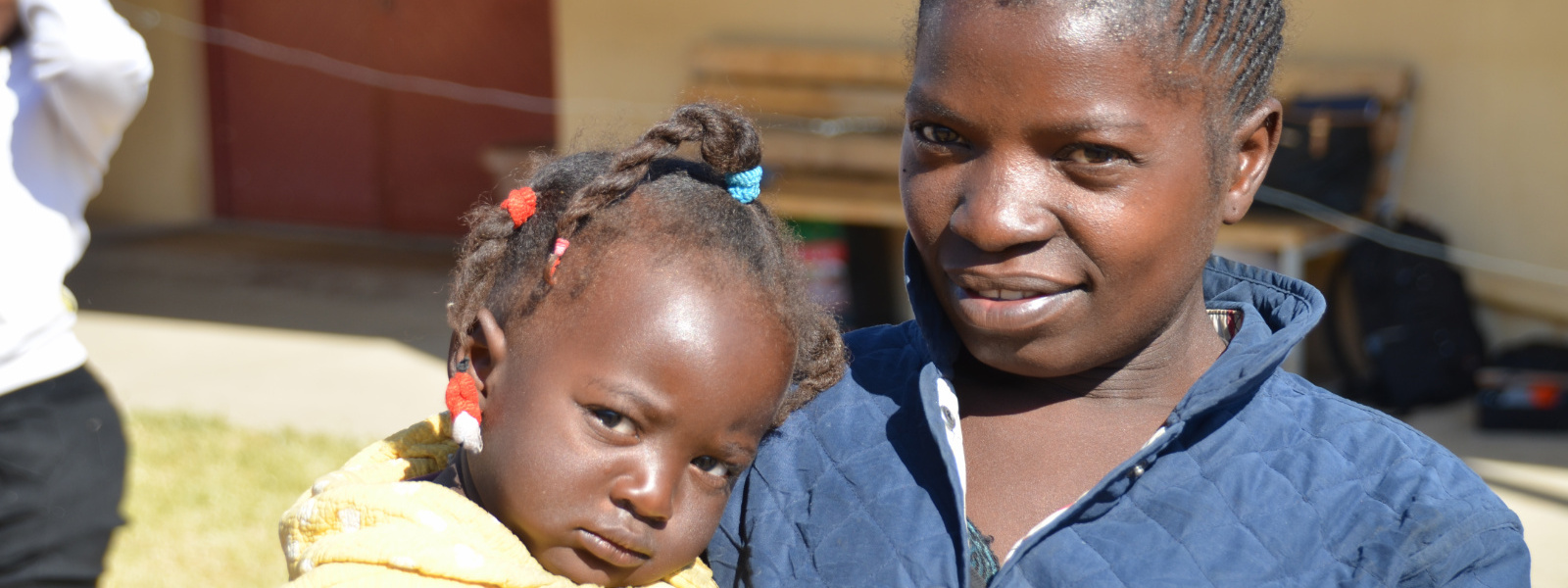 Smiling young woman with pouting child in Angola, client of Hope for Our Sisters