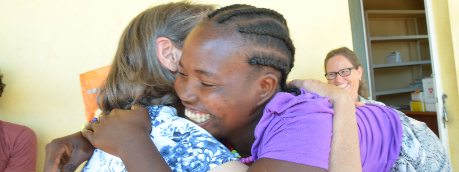 Smiling African woman hugging a Hope for Our Sisters worker